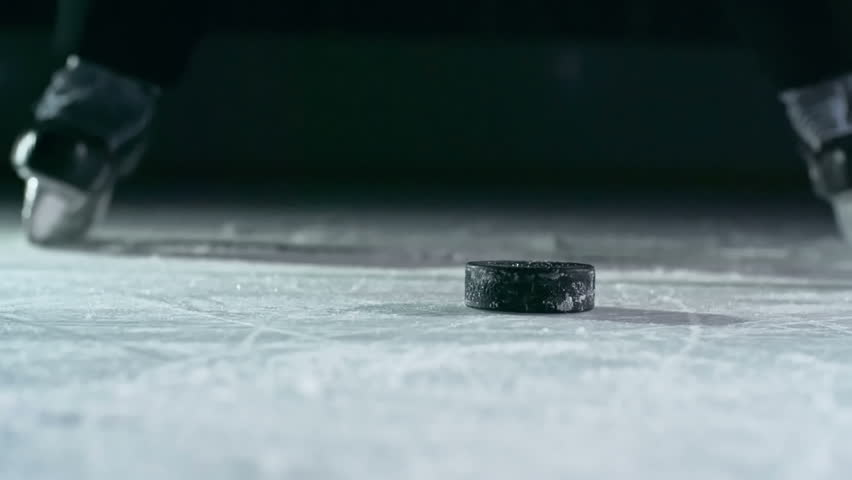 Close-up of hockey puck being struck by hockey player in slow motion | Shutterstock Video #14497141