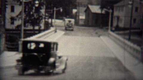 STEEP FALLS, MAINE 1939: Ford model T car driving across new bridge in small town.