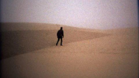 ASTORIA, OREGON 1971: Man walking in blonde yellow sand desert alien landscape.