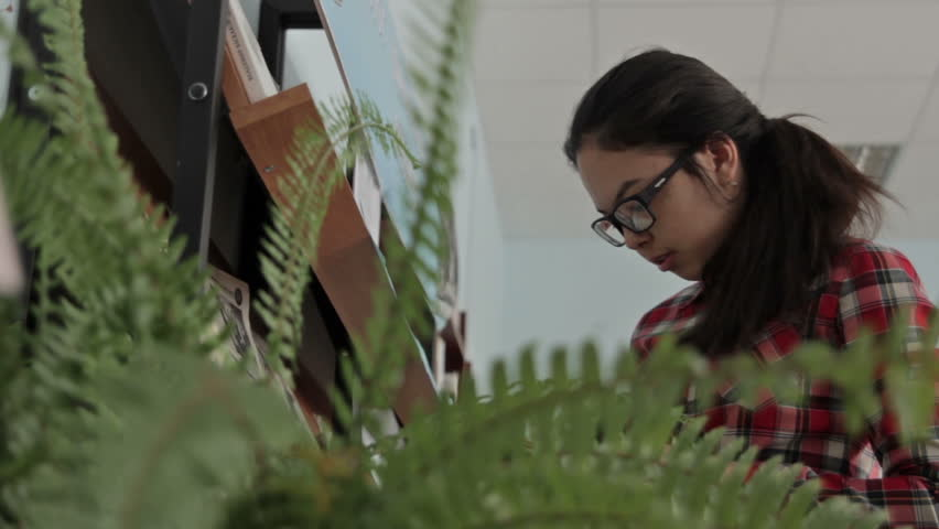 Girl with long hair wearing glasses working in the school library. | Shutterstock HD Video #14563999