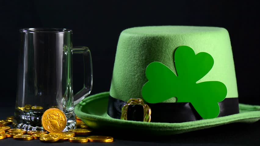 St Patricks Day pouring green beer with green leprechaun hat, gold coins and shamrock against black background, zoom.