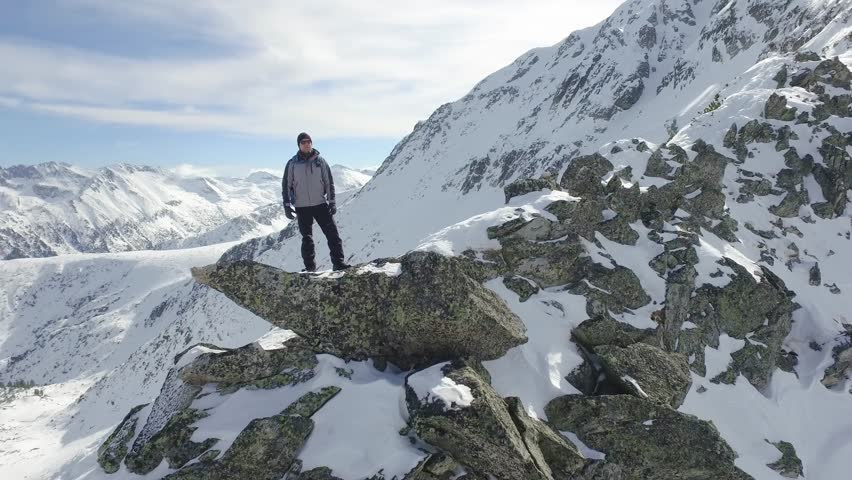 Beautiful Epic Scale Mountain Range Man Standing On Top Of Cliff Edge Snow Winter Landscape Nature Success Accomplishment Opportunity Concept Aerial Flight | Shutterstock HD Video #14596438