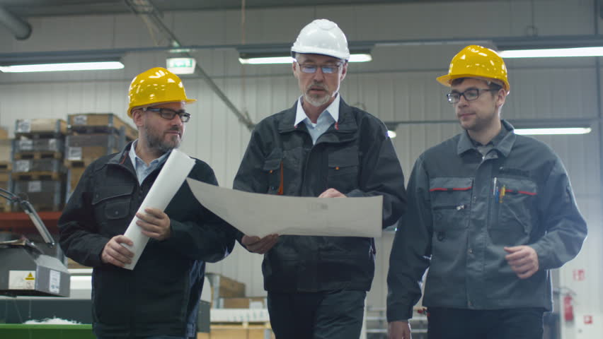 Senior engineer and two workers are walking with papers through the factory space. Shot on RED Cinema Camera in 4K (UHD).