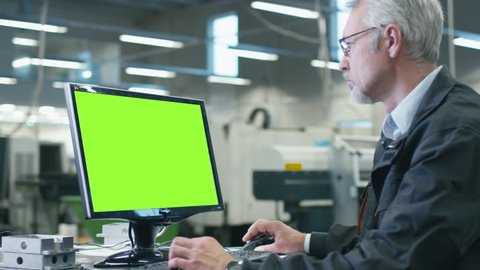 Senior engineer in glasses is working on a desktop computer with a green screen on monitor in a factory. Shot on RED Cinema Camera in 4K (UHD).