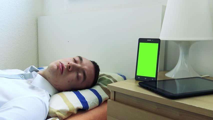 Young man sleeps in bed smartphone on bedside table stock footage young man sleeps in bed smartphone and tablet on bedside table phone green screen watchthetrailerfo