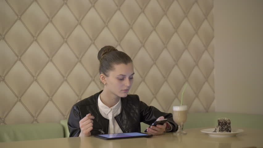 Girl sitting in cafe, using tablet, phone at the table with cake and latte. 4K