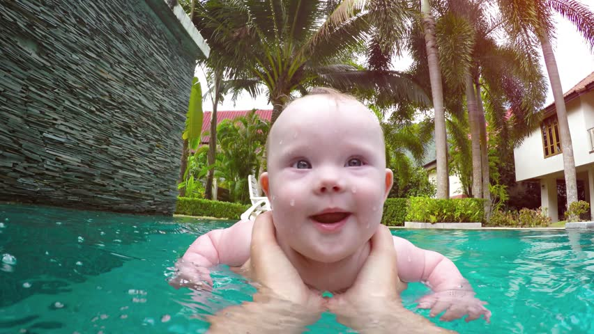 Happy. smiling baby learning to swim with Mommy in an adult sized pool with a backdrop of beautiful palm trees and gardens. UltraHD video