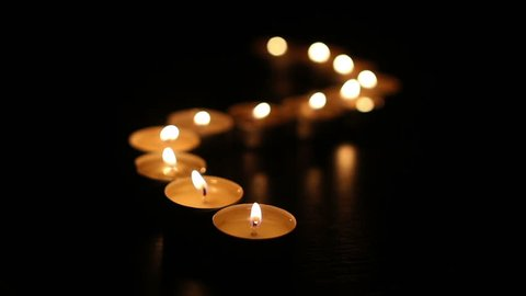 Tea light candles lined up in curved line being lit up one by one.