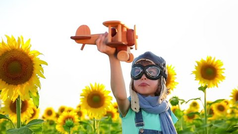 Happy child playing with toy airplane against summer sky background. Slow motion