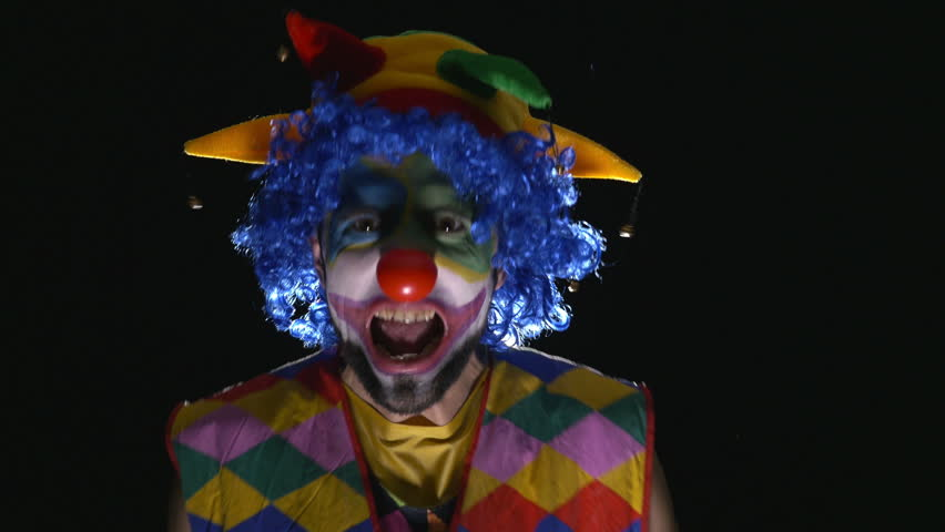 Young hilarious clown making scary faces and laughing