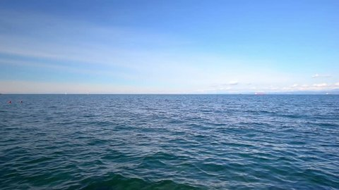 Sea view on the nice summer day: blue sky with small clouds, clean blue sea water and smooth waves,  clear horizon line. Sea, ocean, nature video background for touristic and resort websites.