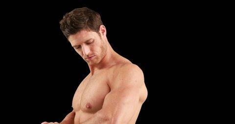 Bodybuilder flexing for the camera on black background