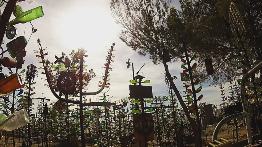 HELENDALE, CALIFORNIA/USA: June 14, 2015- Shot of someone walking through a section of the Bottle Tree Forest-  a free roadside art installation/attraction made of glass bottles arranged whimsically .