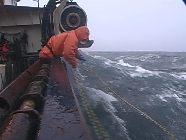 lobster fishermen struggle to attach a rope to a machine on their crab fishing boat during a raging storm.