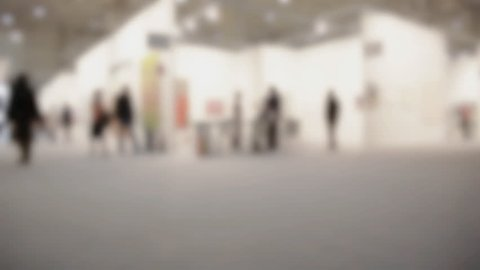View of people walking during an art gallery exhibition visit. Background with an intentional blur effect applied.