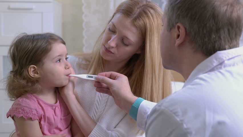 Doctor is measure the temperature of little girl.