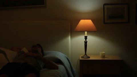 Person turns off night lamp while laying down in bed thinking