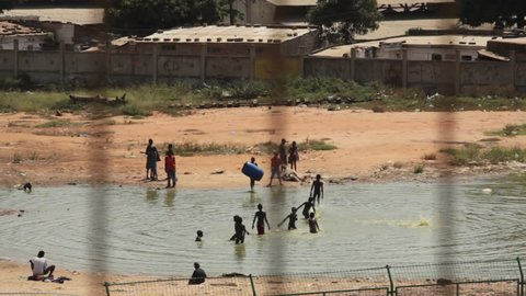 Luanda, Angola - 2011 - Looking down, through a metal fence, at the pond behind a township/poor houses where children are frolicking in the water.