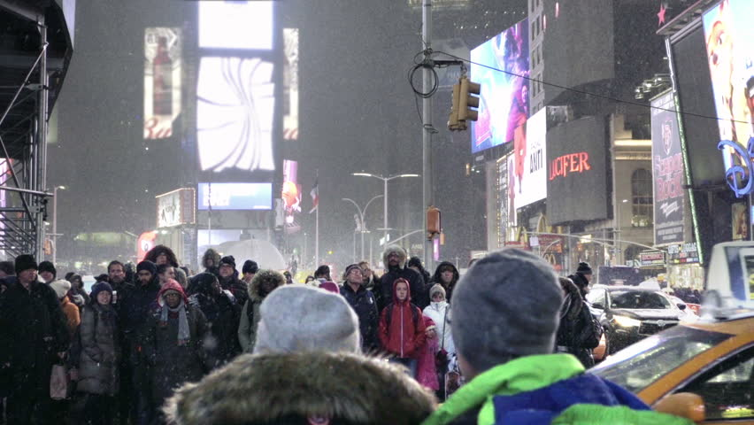 NEW YORK - FEB 15, 2016: snowing with people waiting taxis crossing, taxicabs driving across crosswalk in Times Square winter NYC. Tourism is a major industry for Manhattan during the holidays.   Shutterstock HD Video #14752429
