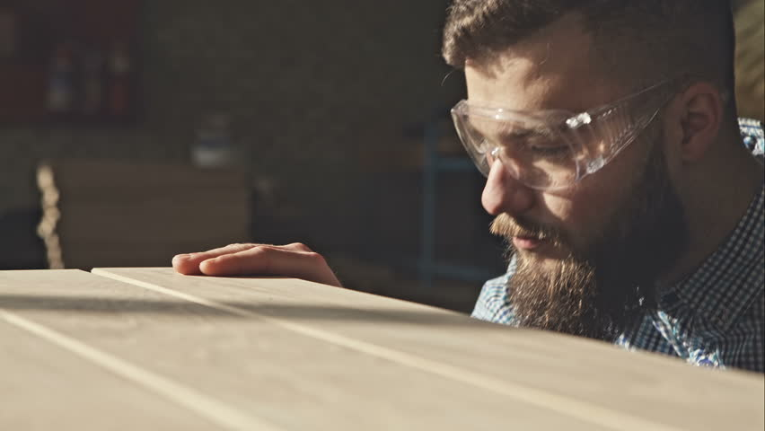 A young bearded carpenter checks the quality of the boards in the sun. RAW video record. | Shutterstock HD Video #14773285