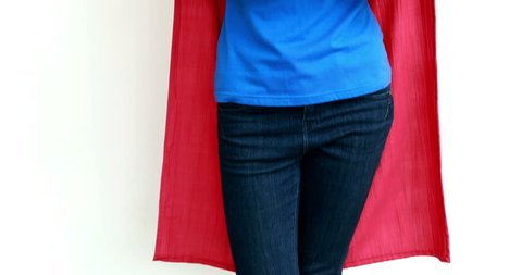 Serious woman with superman disguise against white background