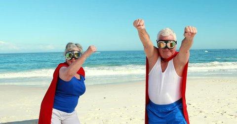 Senior couple pretending to be superhero on the beach