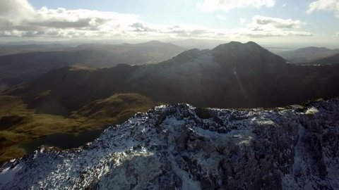 Aerial shot circling Crib Goch, Snowdonia, UK. Lakes visible initially, then Mount Snowdon comes into view at the end of the shot.