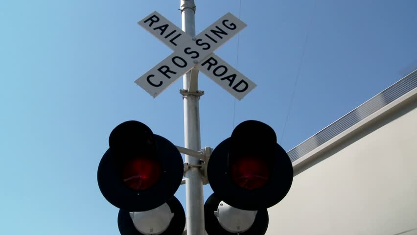 Red lights flash at a railroad crossing.