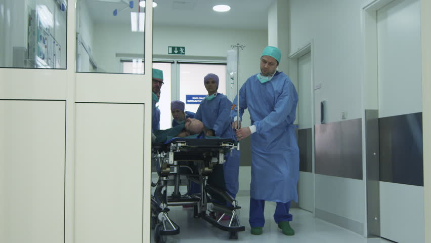 Hospital Emergency Team Carrying Stretcher with Patient through Hospital Hall. Shot on RED Cinema Camera.