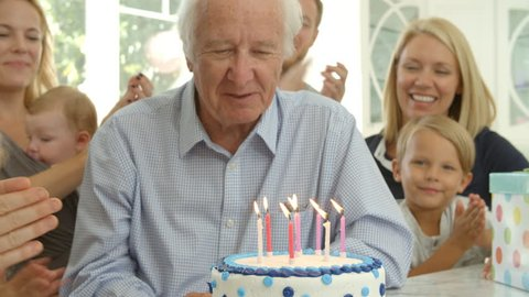 Grandfather Blows Out Candles On Birthday Cake Shot, Slow Motion