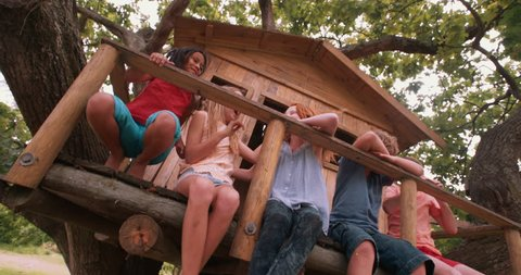 Group of children playing in a treehouse in a huge tree and tickling together