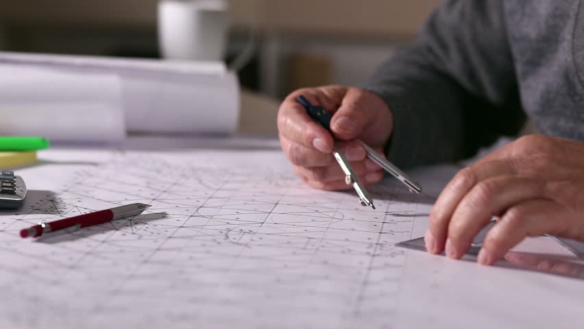 Senior architect working on construction blueprint in office he senior architect working on construction blueprint in office he draws with a divider and ruler malvernweather Choice Image