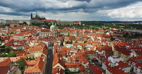 Flying through the old town of Prague, the Czech Republic on a sunny day with dark clouds. Beautiful view of Prague Castle and the Cathedral of St. Michael in 4k.