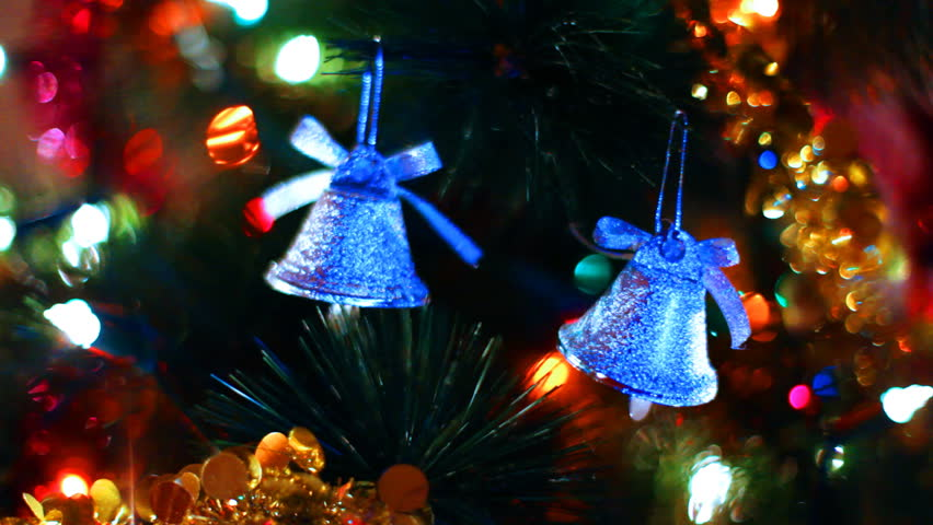 two blue toy bells hang on Christmas tree among of blinking colored garlands, close-up