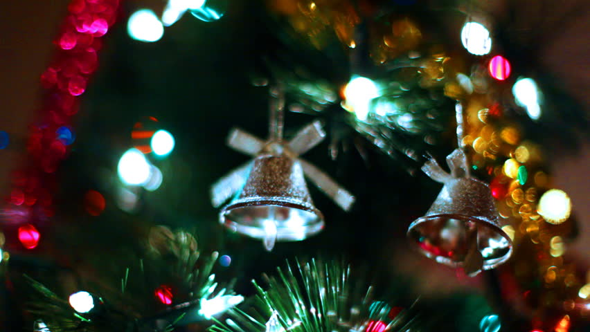 two gold toy bells hang on Christmas tree among of blinking colored garlands, close-up #1484449