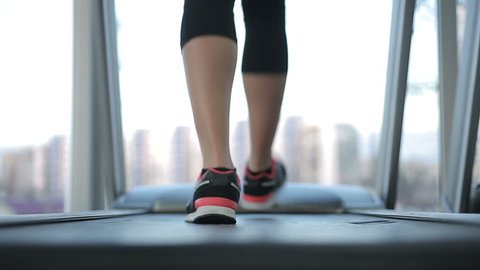 Back view of female legs walking and running on treadmill gym, motivated woman training. Fitness person doing cardio exercises, goal oriented, weight loss inspiration. Healthy activity in sport club