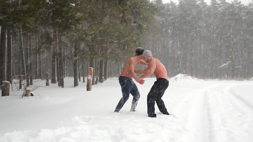 Two bare-chested guys wrestle practicing hip throw at outdoor sportsground in winter forest.