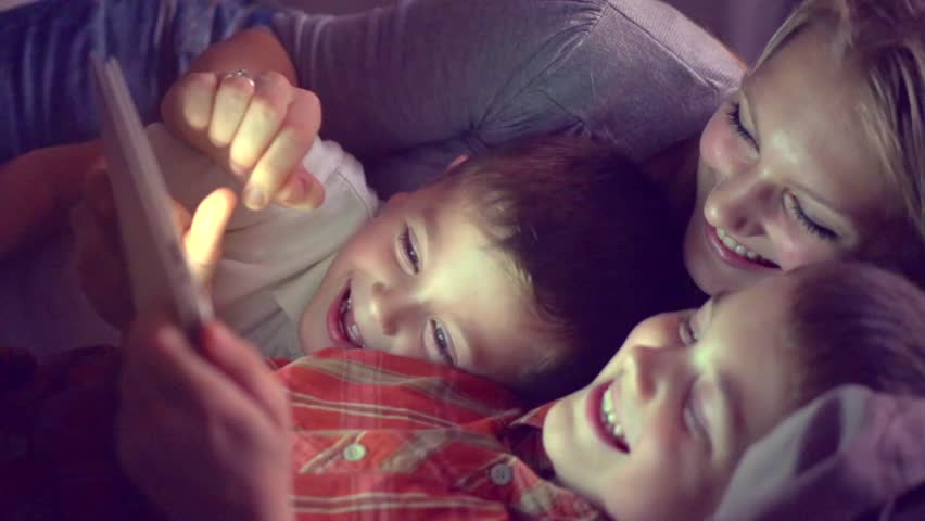 Happy family- mother and Two kids lying down on the sofa and using tablet pc at night. Family watching movie on tablet computer in a dark room, playing games. HD 1080p, slow motion 240 fps