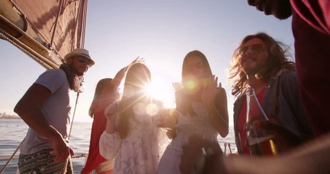 Group of friends enjoying a party on a yacht, laughing and dancing while holding drinks at sunset with golden sunflare in Slow Motion