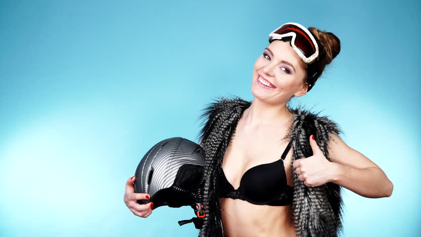 Woman Sexy Hot Skier Girl Wearing Black Bra Fur Vest Ski Googles Holding Helmet Winter Sport Activity Beautiful Seductive Sportswoman On Blue Studio Shot