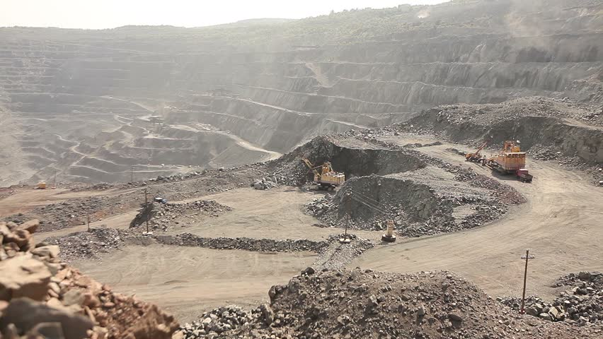 Large, open-pit iron ore mine showing the various layers of soil and iron rich ore,  industrial exterior, ore mining quarry, sunny day, summer, mining of iron