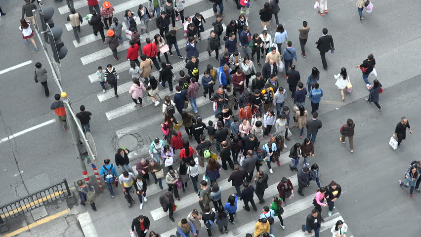 SHANGHAI, CHINA - 31 OCTOBER 2015: People cross a busy zebra to reach Nanjing Road, one of the most popular (and therefore busiest) shopping streets in Shanghai, China