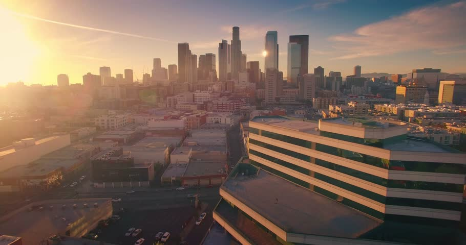 Aerial view of city of Los Angeles downtown skyline at sunset. Camera flying forward. 4K UHD.