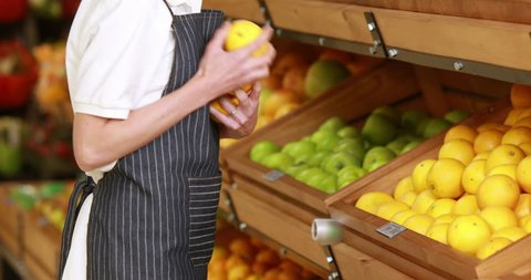 Portrait of smiling Caucasian female worker stocking lemons in grocery store