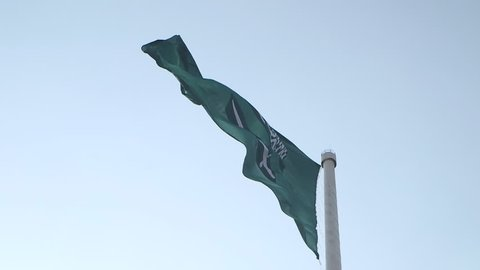 Saudi Arabian Flag. Shot of the Saudi flag against a blue sky. The flag billows in the breeze in slow motion.