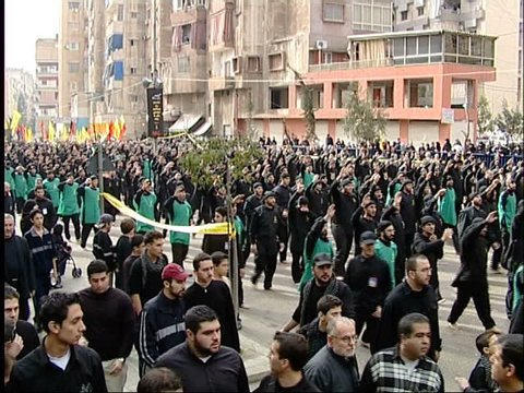 Dahieh, Beirut, Lebanon - 2005 - Hezbollah's Ashoura commemorations. A procession of men beat their chests in ritual mourning while chanting slogans commemorating the martyr Hussein and Hezbollah.