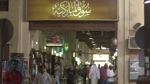 Kuwait Souk. 2013 Medium shot of the entrance sign of Souk Al Moubarakiya written in Arabic calligraphy. Shoppers and traders walk in and out of the souk.