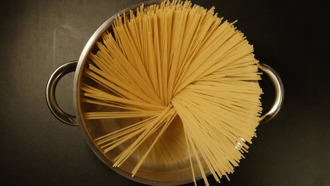 TOP VIEW: A cook puts down a spaghetti in a steel pot (round)
