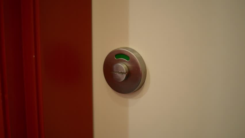 Close-up of a public toilet door lock which is green indicating cubicle is empty. Man opens door, enters, closes door and turns lock to red indicating cubicle is occupied or busy.