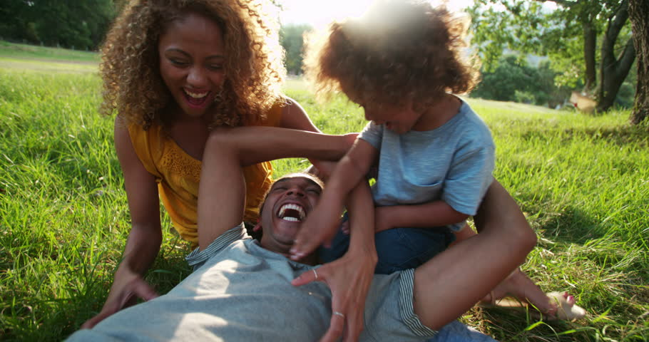 Young african-american family spending quality time toghether and relaxing in the beautiful picturesque park in the late afternoon